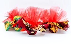 stoffe colorate colori assortiti da Tanzania tipo Kitenge, con dentro confetti e tulle a mò di sacchettino, bomboniera solidale Africa