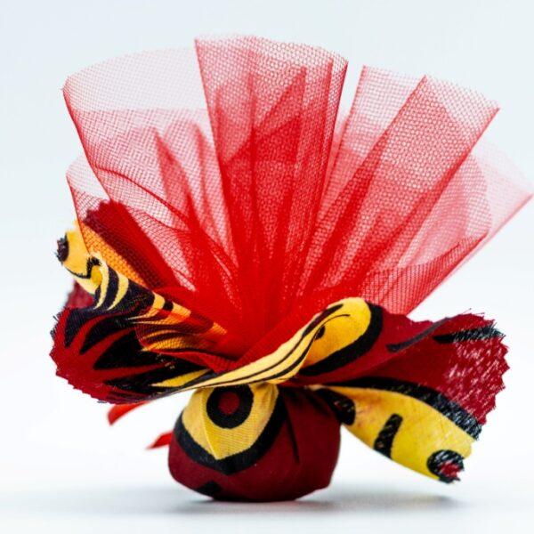 stoffa colorata rossa e gialla da Tanzania tipo Kitenge, con dentro confetti e tulle a mò di sacchettino, bomboniera solidale Africa