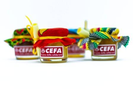 vasetti di miele solidale come bomboniera per sostenere apicoltura in Africa. Il vasetto di 40 gr è coperto da un colorato pezzo di stoffa africana, chiusi da un nastrino giallo. Nella foto 4 vasetti di tipi diversi di miele, coperti da stoffe di 4 colori diversi.