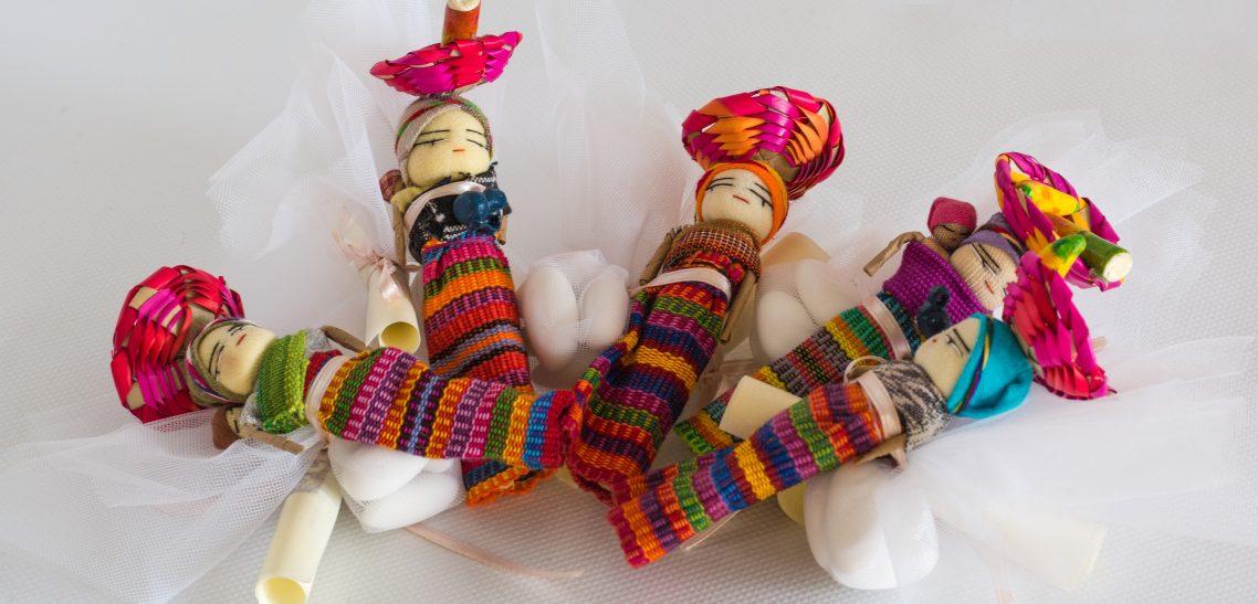 bomboniere cresima con confetti in sacchetti di tulle colorati e decorati con bamboline e oggetti tradizionali (cestini sul capo, bimbi sulle spalle, animali, frutta) provenienti dal Guatemala con calamita sul retro e pergamena personalizzata.