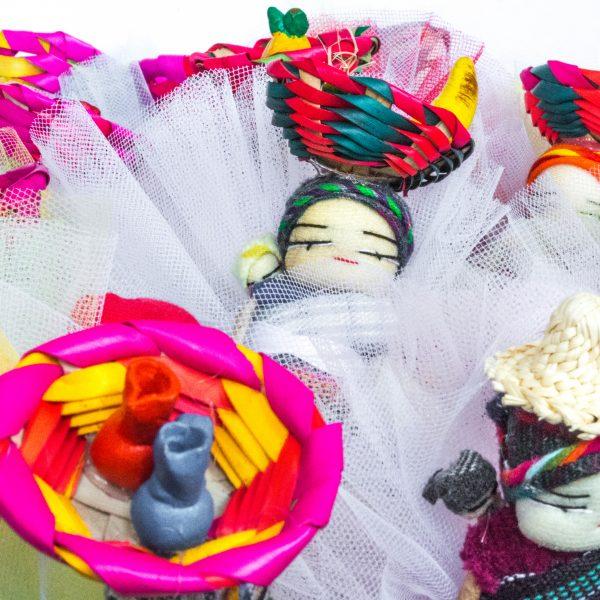 bomboniere cresima con confetti in sacchetti di tulle colorati e decorati con bamboline abbellite con cesti in testa vivaci e differenziati provenienti dal Guatemala con calamita sul retro.
